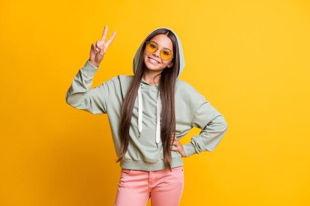 Foto van kleine mooie persoon toont handvinger v-teken bril geïsoleerd op gele kleur achtergrond
