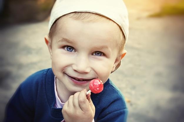 Foto van kleine peuterjongen die snoep op stok, lolly eet, die in glb in zonnige dag draagt.