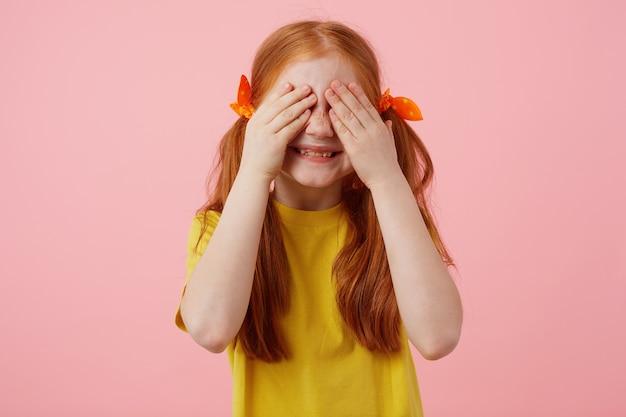 Foto van kleine sproeten roodharige meisje met twee staarten, glimlacht en ogen bedekt met palmen, draagt in geel t-shirt, staat op roze achtergrond.