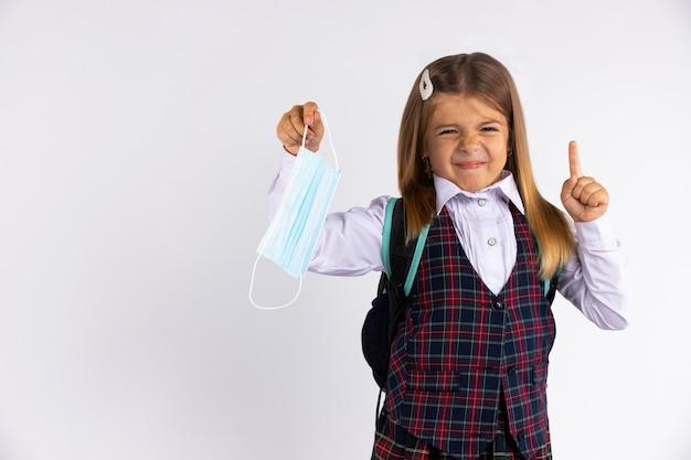 Foto van kleine student school meisje kleding school houdt niet van epidemische regels wil geen gezichtsmasker dragen.