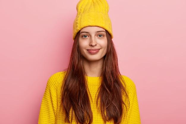 Foto van knap vrouwelijk model heeft lang donker haar, kijkt recht in de camera, draagt een levendige gele hoed en gebreide trui, in goed humeur, geïsoleerd op roze achtergrond.