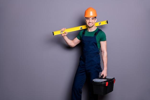 Foto van knappe aantrekkelijke hout kerel geschoolde ingenieur houden maatregel rek gereedschapskist start werkkleding t-shirt veiligheid tuinbroek beschermende helm bril geïsoleerd grijze muur
