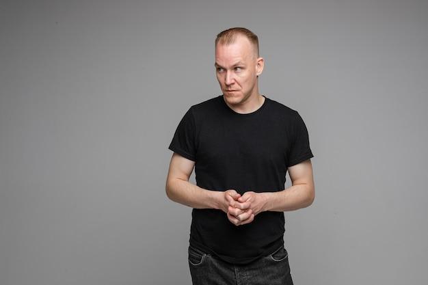 Foto van knappe blanke man houdt handen bij elkaar ziet er met verbaasd zicht geïsoleerd op een grijze achtergrond