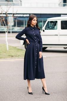 Foto van knappe blanke vrouw met lang golvend bruin haar en mooi gezicht in zwarte jurk en zwarte schoenen buiten