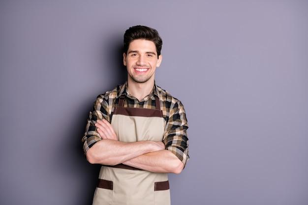 Foto van knappe donkerbruine man armen gekruist vriendelijk glimlachen positief goed humeur professionele werknemer slijtage schort geruite overhemd geïsoleerde grijze kleur muur