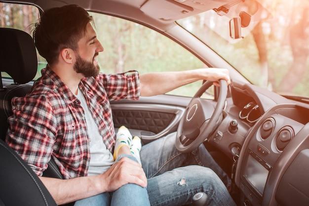 Foto van knappe en zelfverzekerde man die de auto bestuurt. hij kijkt op de weg.
