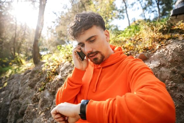 Foto van knappe ernstige jonge sport fitness man loper buiten in park praten door mobiele telefoon horloge klok kijken.