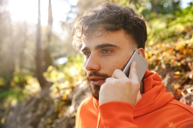 Foto van knappe ernstige jonge sport fitness man loper buiten in park praten via de mobiele telefoon.