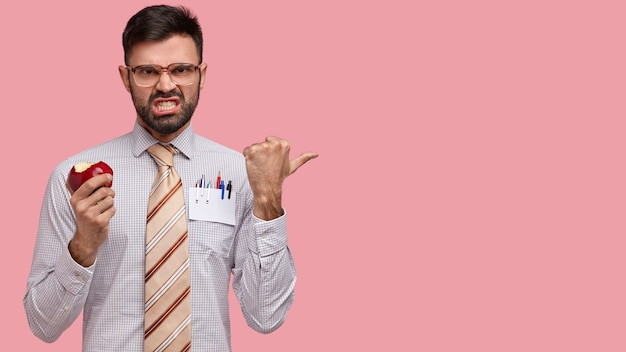 Foto van knappe ervaren mannelijke manager grijnst gezicht, klemt zijn tanden, is ontevreden en boos, draagt elegante outfit