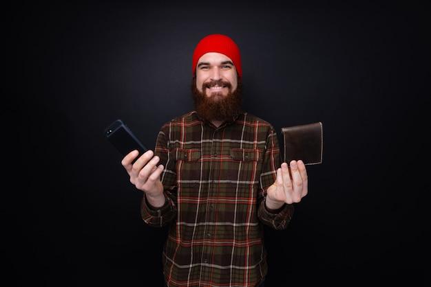 Foto van knappe gebaarde manshowing zijn telefoon en portefeuille die zich over donkere muur bevinden