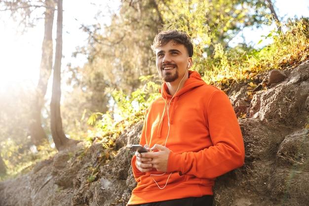 Foto van knappe gelukkige jonge sport fitness man loper buiten in park luisteren muziek met koptelefoon met behulp van mobiele telefoon.