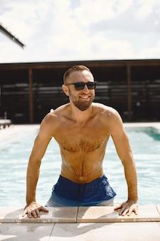 Foto van knappe glimlachende man in zwembad. zonnebaden in badplaats.