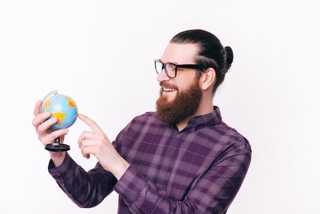 Foto van knappe jonge man met baard wijzend op wereldbol op witte achtergrond