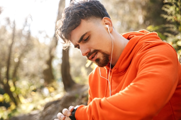 Foto van knappe jonge sport fitness man loper buiten in park luisteren muziek met koptelefoon kijken horloge klok.