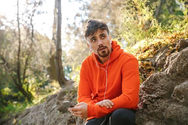 Foto van knappe jonge sport fitness man loper buiten in park luisteren muziek met koptelefoon met behulp van mobiele telefoon.