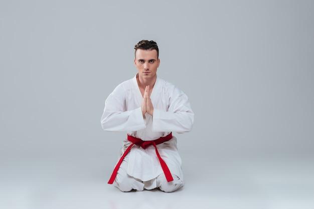 Foto van knappe jonge sportman zittend op de vloer in kimono terwijl hij poseert over grijze achtergrond. camera kijken.