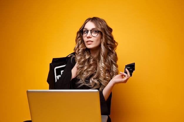 Foto van knappe jonge vrouw met zwarte creditcard en nieuwe boodschappentassen in de buurt van de computer
