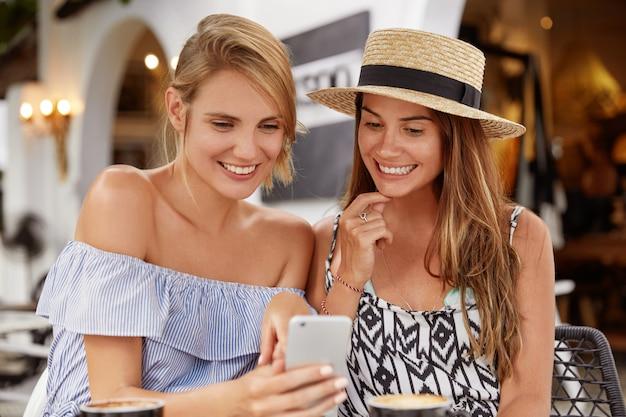 Foto van knappe jonge vrouwen in zomerkleding, samen vrije tijd doorbrengen, film kijken op smartphone of videogesprek voeren, koffie drinken in een restaurant, snelle internetverbinding gebruiken.