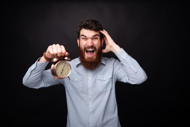 Foto van knappe jongen met baard, vertragen, woirried over zijn deadline, staande op een donkere achtergrond