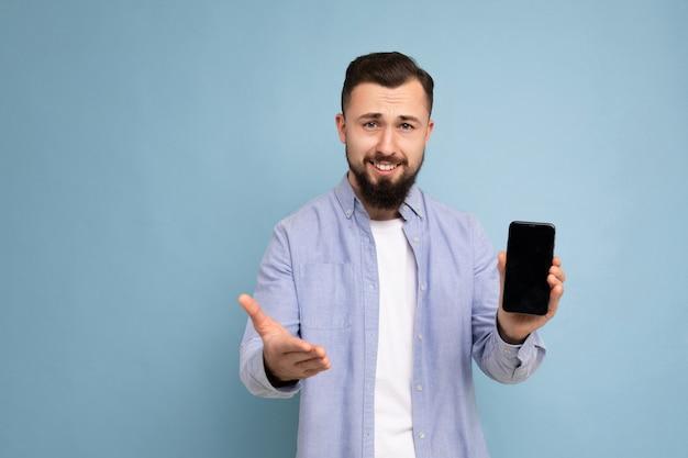 Foto van knappe knappe jonge brunette ongeschoren man met baard die een casual wit t-shirt draagt