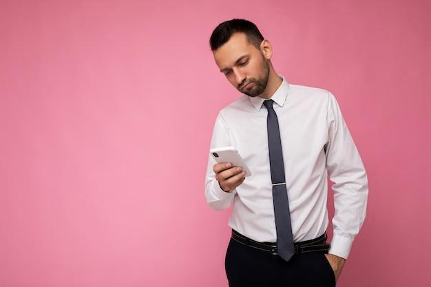 Foto van knappe knappe man met casual wit overhemd en stropdas geïsoleerd op roze achtergrond met lege ruimte in de hand houden en met behulp van mobiele telefoon messaging sms camera kijken. kopieer ruimte