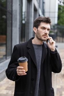 Foto van knappe man 20s met behulp van mobiele telefoon, tijdens het wandelen buiten met afhaalkoffie