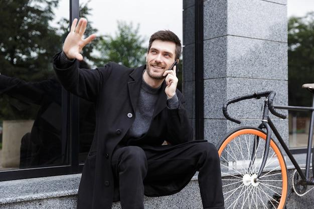 Foto van knappe man 20s met behulp van mobiele telefoon, zittend buiten met fiets