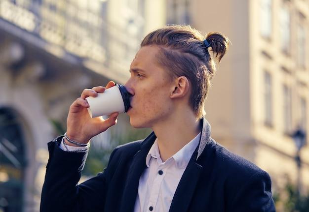 Foto van knappe man die op straat loopt en opzij kijkt terwijl hij een kopje koffie vasthoudt.