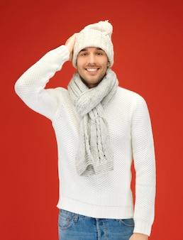 Foto van knappe man in warme trui, muts en sjaal.