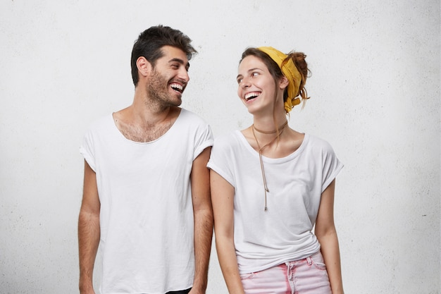 Foto van knappe man met donker haar en schattig vrouwtje kijken elkaar met een brede glimlach wordt vrolijk om elkaar te ontmoeten.