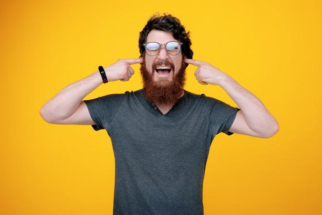 Foto van knappe man met gesloten ogen, schreeuwen en vinger in zijn oren, permanent op geel