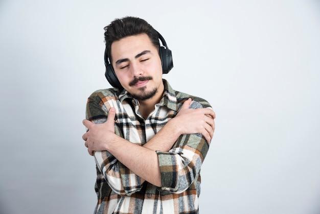 Foto van knappe man met koptelefoon die zichzelf vasthoudt over witte muur.