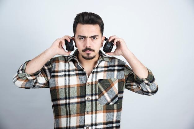 Foto van knappe man met koptelefoon staan en kijken uit over witte muur.