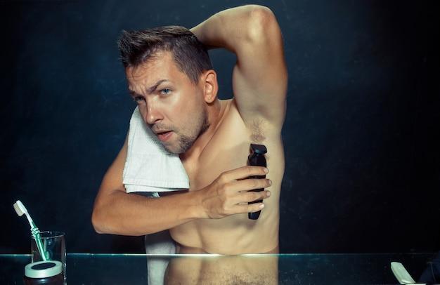 Foto van knappe man zijn oksel scheren. de jonge man in de slaapkamer zit thuis voor de spiegel. menselijke huid en levensstijl concept