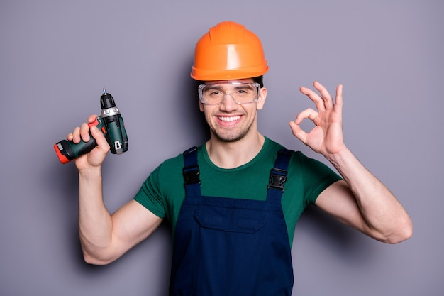 Foto van knappe mannelijke werknemer kerel geschoolde ingenieur houden elektrische boor toont okey symbool slijtage t-shirt veiligheid tuinbroek beschermende helm bril geïsoleerd grijze muur