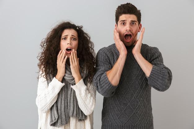 Foto van knappe paar man en brunette vrouw schreeuwen en aanraken van gezicht, geïsoleerd over grijze muur