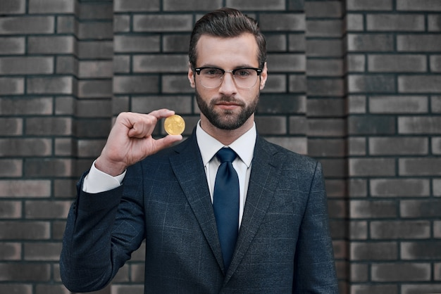 Foto van knappe rijke zakenman in pak met gouden bitcoin Premium Foto