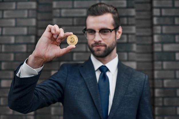 Foto van knappe rijke zakenman in pak met gouden bitcoin