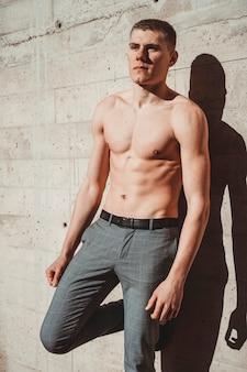 Foto van knappe shirtless man buiten voor een muur