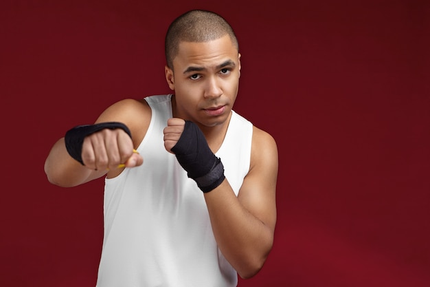 Foto van knappe sterke atletische jonge gemengd ras man bokser met gespierde armen permanent in sportschool met lege muur, vuisten voor zich houden, klaar om zijn tegenstander te slaan tijdens bokswedstrijd