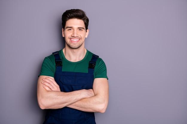 Foto van knappe viriele spieren kerel houden armen gekruist zelfverzekerd beste handarbeider geschoolde ingenieur dragen groen t-shirt blauwe veiligheid tuinbroek geïsoleerde grijze muur