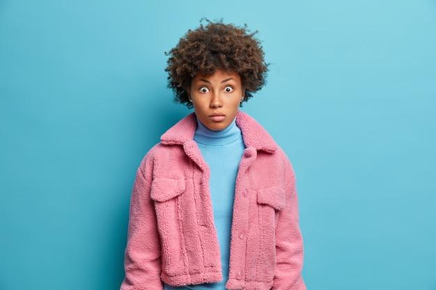 Foto van knappe volwassen vrouw met ogen die uit de verbazing staren naar de camera, hoort schokkend nieuws draagt blauwe coltrui en roze jas poseert binnenshuis. mooi etnisch meisje voelt zich verward geschokt shock