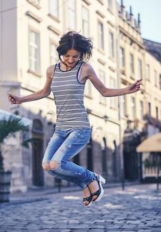 Foto van knappe vrouw springen in de straat