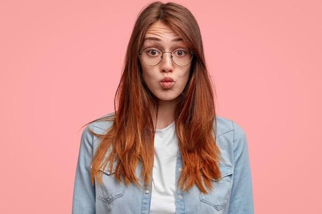 Foto van knappe vrouwelijke tiener met sproeten huid, lippen rond houdt, grimas naar camera maakt, draagt denim overhemd, staat alleen tegen roze achtergrond.
