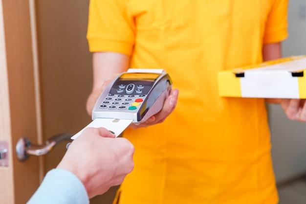Foto van koerier in geel t-shirt met doos met pizza en verkooppunt op roze Premium Foto