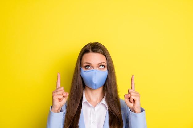 Foto van kraag meisje wijsvinger copyspace demonstreert covid quarantaine nieuws draag blauw blazer pak ademhalingsmasker geïsoleerd over heldere glans kleur achtergrond