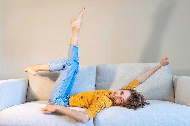 Foto van krankzinnige vrolijke positieve vrouw in goed humeur die haar benen en armen opheft