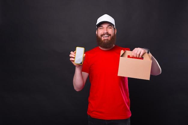 Foto van lachende bebaarde man in rood t-shirt en witte pet lunchdoos houden en smartphone tonen