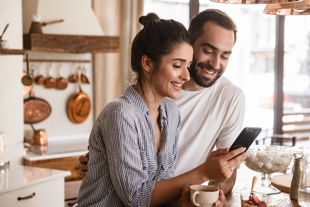 Foto van lachende brunette paar man en vrouw die koffie drinken en mobiele telefoon gebruiken tijdens het ontbijt in de keuken thuis