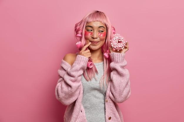 Foto van lachende goog uitziende vrouw heeft zoetekauw en kijkt met eetlust op heerlijke donut, draagt haarkrulspelden, heeft roze kapsel